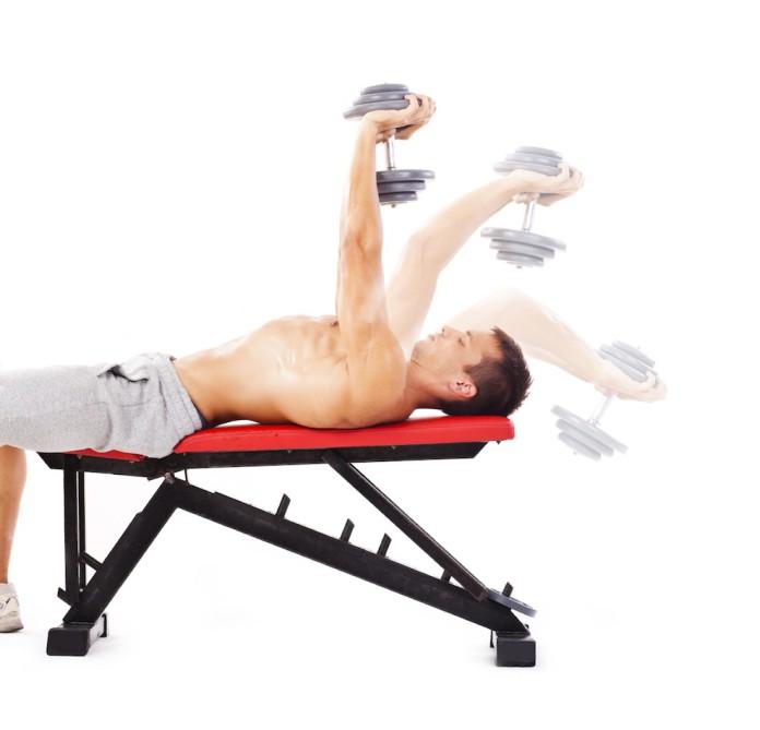 Sportler trainiert auf einer BAnk Überzüge mit der Kurzhantel