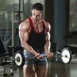 Sportler trainiert im Fitnesscenter mit der Langhantel Unterarm-Curls