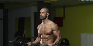 Sportler trainiert mit der Langhantel den Unterarm-Curl
