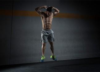 Ein sehr definierter Kraftsportler macht einen Strecksprung vor einer grauen Wand