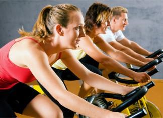 Drei Sportler beim Spinning im Fitness-Studio