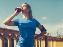 Eine Frau im sportlichen Outfit trinkt einen Eiweißshake