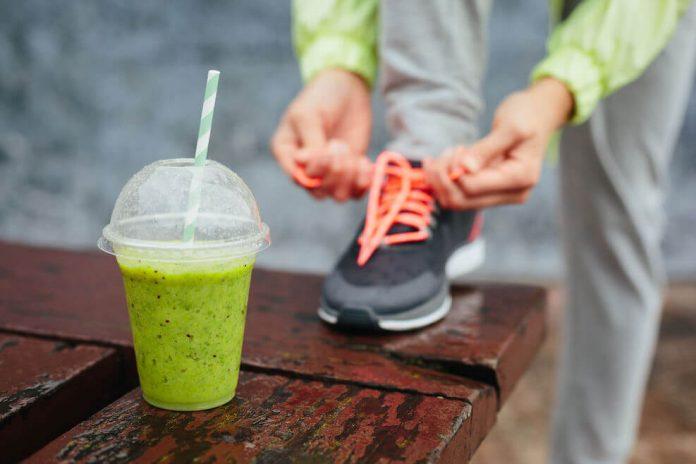 Ein Sportler bindet sich seinen Laufschuh zu und im Vordergrund ist ein Shake zu sehen