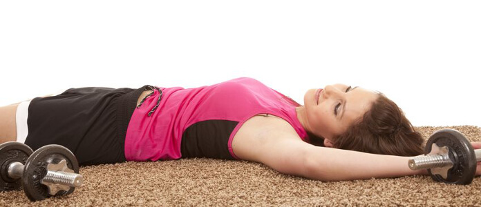 Eine sportliche Frau schläft auf dem Boden mit Hanteln in der Hand
