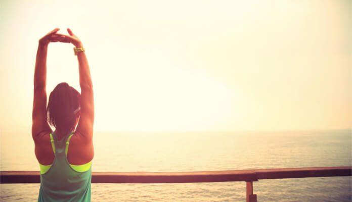 Eine Frau steht auf einem Steg und dehnt sich während sie aufs Meer blickt