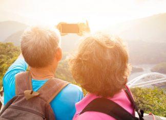 Eine ältere Frau und ihr Mann stehen auf einem Berg in wilder Natur und machen ein Selfie
